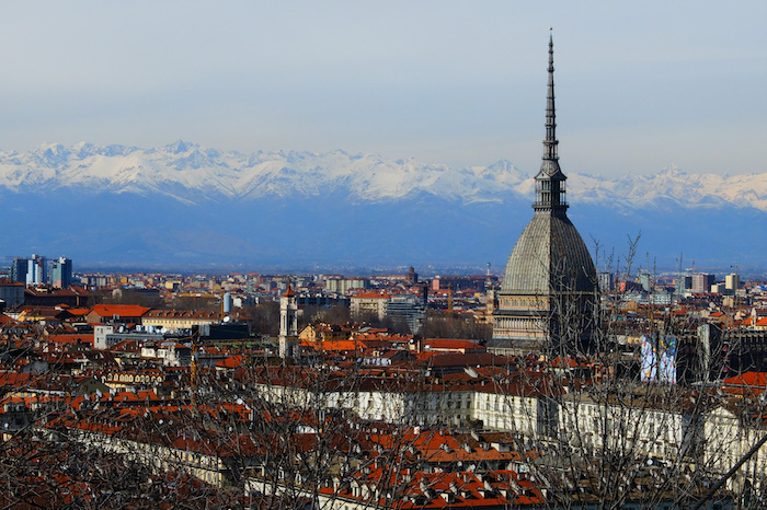 view of the Mole Antonelliane in Turin with the mountains in the background