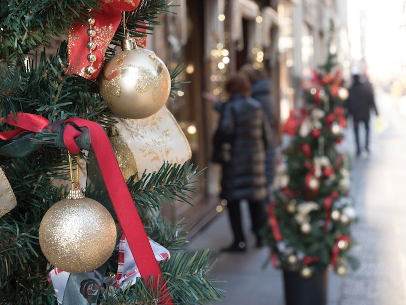 close-up of a christmas tree in the street with people walking in the background