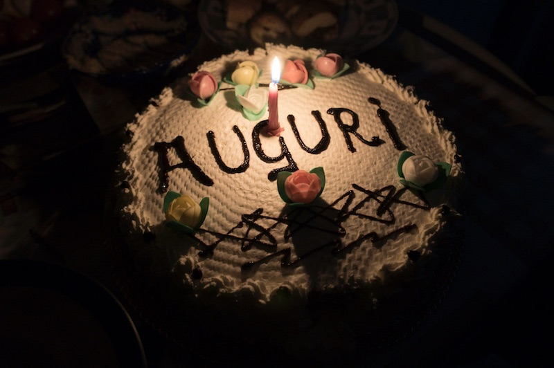 """cake with one candle on it and the word """"auguri"""" written with chocolate"""