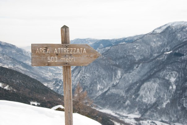 wooden sign on top of a mountain with snow all around