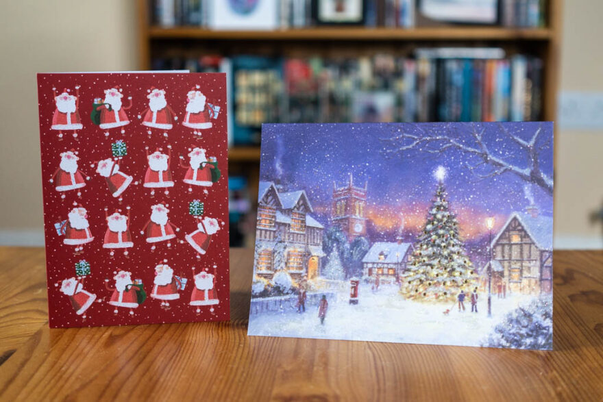 two christmas cards on a wooden table, the first one is red with lots of santa drawings, the second shows a town square covered in snow in the evening with a Christmas tree at the centre