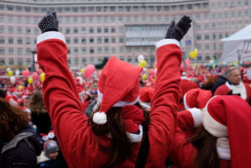 view from behind of a person dressed as santa with her arms up in the air, celebrating in front of a big crowd of people alldressed up as santas