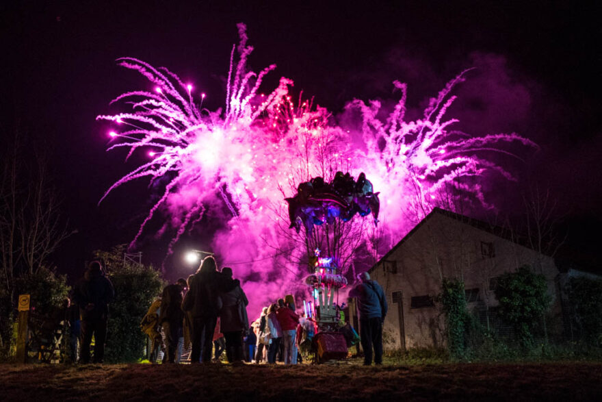purple fireworks in the background and silhouettes of people looking in the foreground