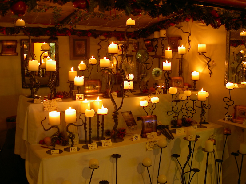 multiple candles burning inside a shop, creating a warm light and atmosphere