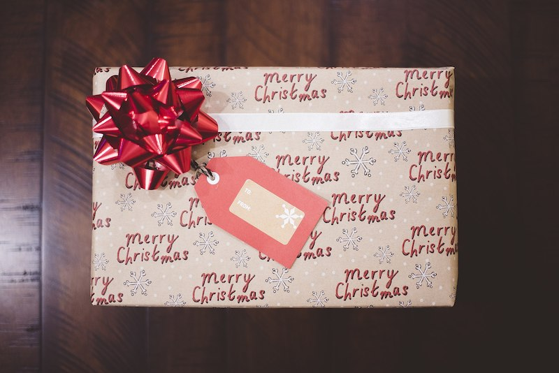 present wrapped with christmas themed paper and red bow