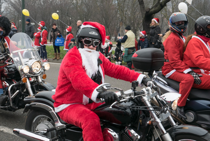 man dressed as santa clause on his harley davidson motorcycle, wearing black goggles and a black helmet