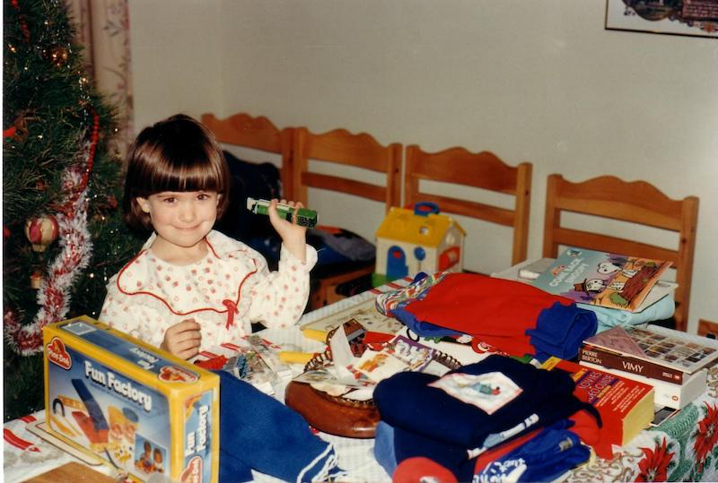 kid with various toys and gifts around her