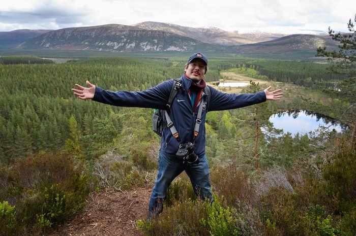 happy man with open arms, forest and mountains in the background