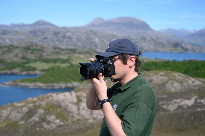 young man taking a photo with a reflex type camera, with hills and lakes in the background