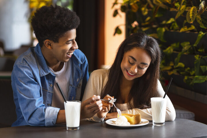 young man and woman smiling at at restaurant while eating cake from the same plate