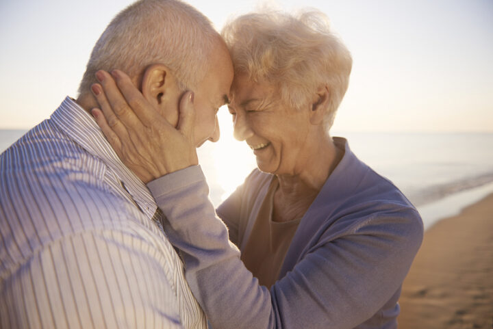 elderly woman holding her husband head, both smiling, on the beach near sunset time