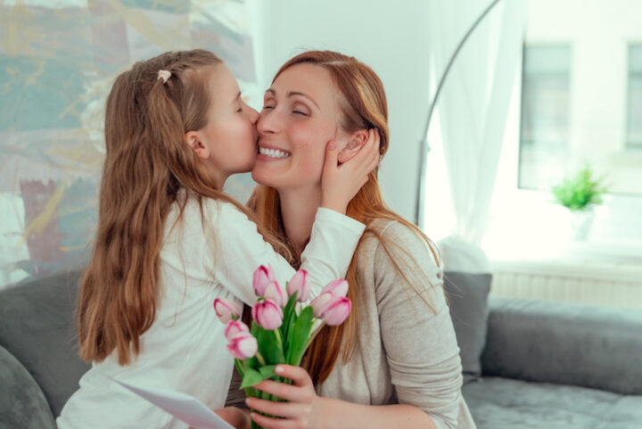 surprising mom with love message from her little daughter and nice pink flowers for mother's day