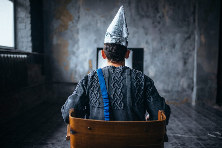 person sitting with a tinfoil hat, view from the back