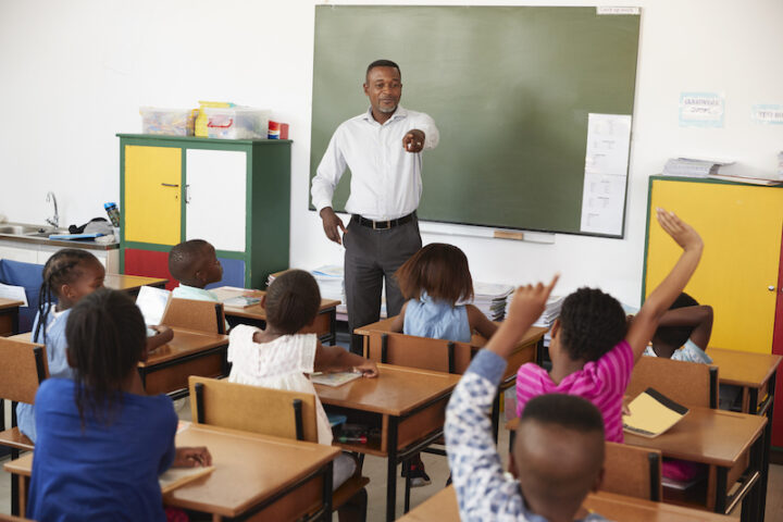 kids raising hand in front of their teacher in class