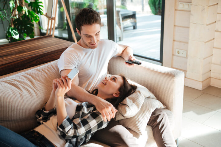 woman lying on the couch on her boyfriend's legs, looking at each others