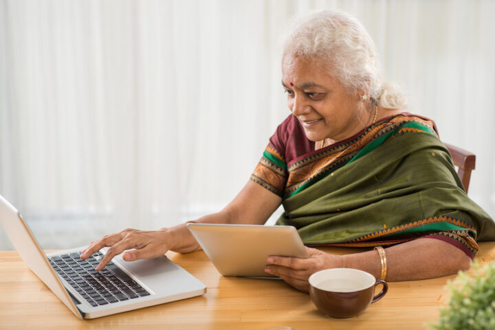 elderly Indian woman using a computer and a tablet