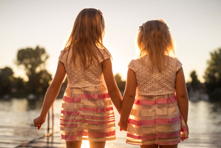 two girls holding hands at sunset