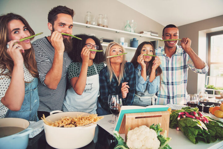 five adults being silly by sniffing an asparagus in the kitchen