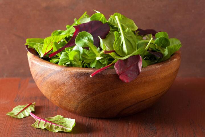 wooden salad bowl full of green leaves