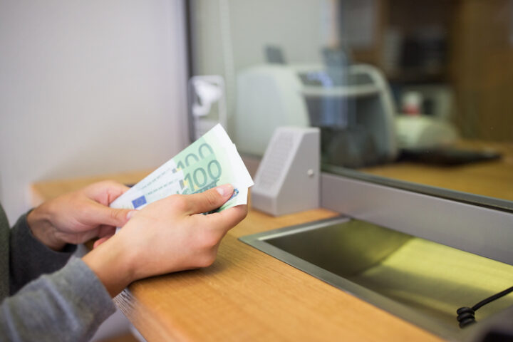 hands holding cash at a counter