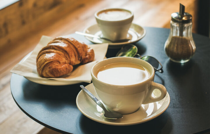 cup of coffee and croissant on a bar table
