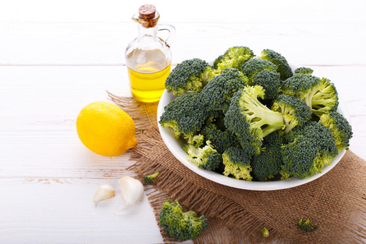 broccoli on a plate with a lemon and olive oil bottle