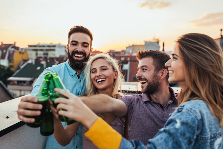 group of friends laughing, smiling and toasting with bottles of beer on a rooftop at sunset