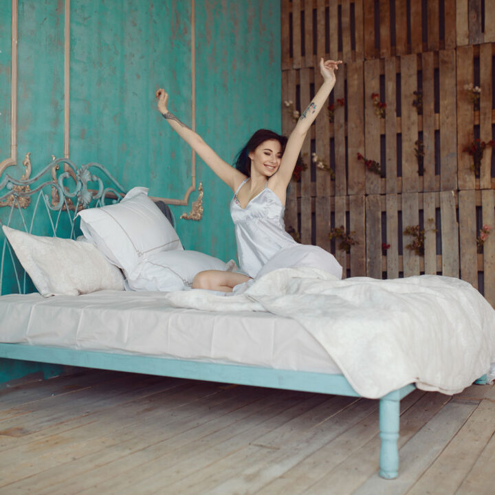 smiling woman stretching on bed after waking up