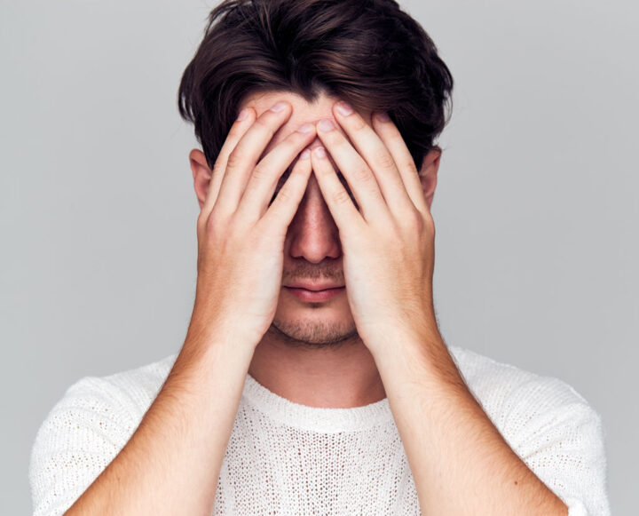 man covering his face with his hands in shame