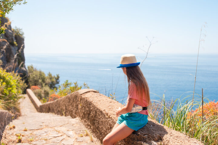 girl sitting next to stairs in a sunny costal location
