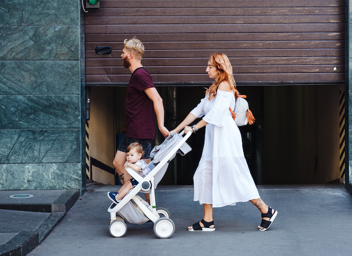couple walking with child in pushchair