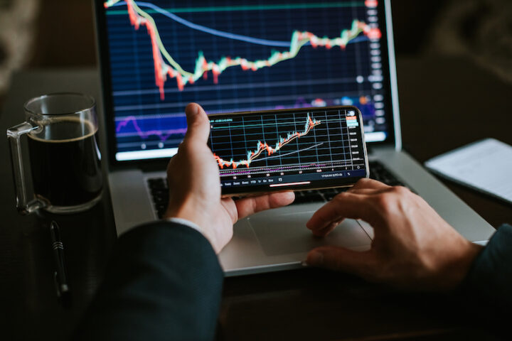 stock market screen and hands holding smartphone