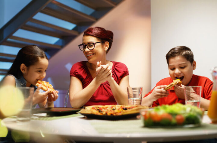 mother and children eating pizza at home