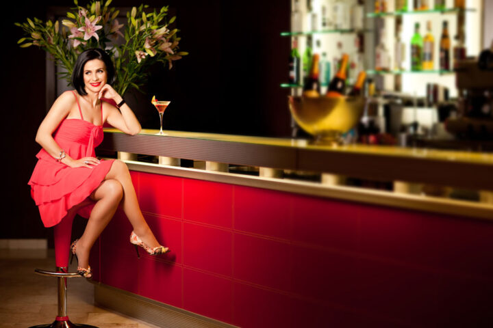 smiling woman with red dress sitting at the bar