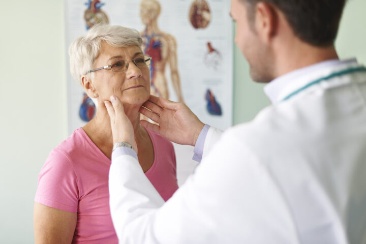 doctor touching woman's neck