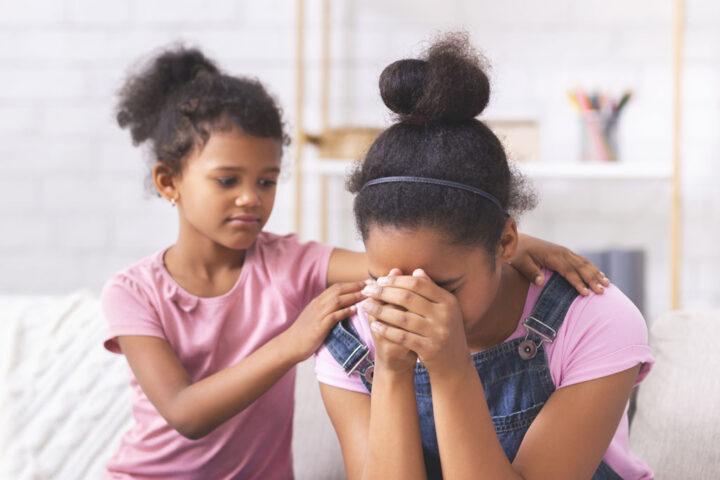 young girl comforting older sister