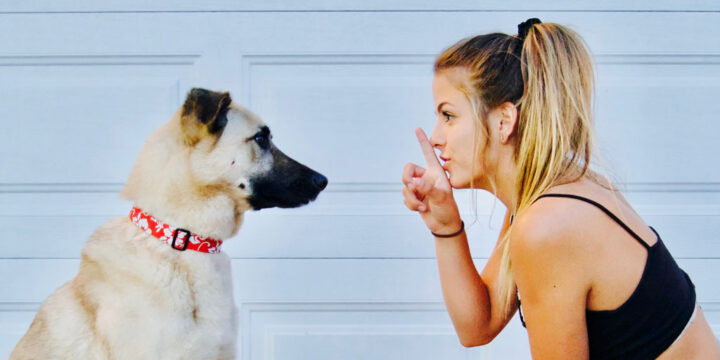 woman showing silence sign to her dog