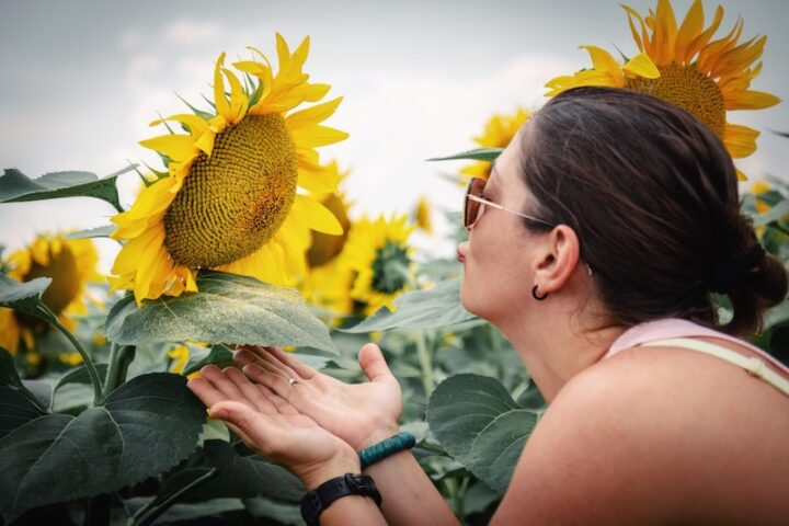 woman looking at a sunflower