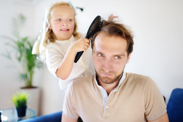daughter brushing dad's hair