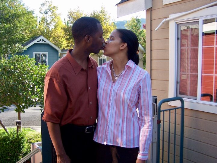 husband and wife kissing outside their house