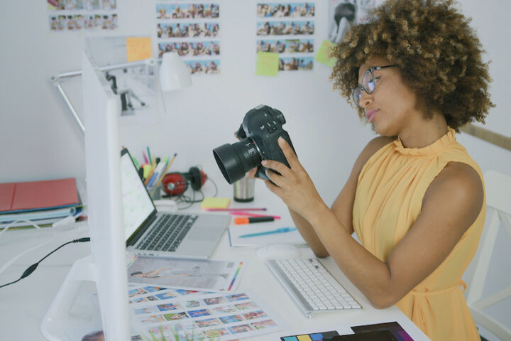 woman looking at her camera sitting on a desk