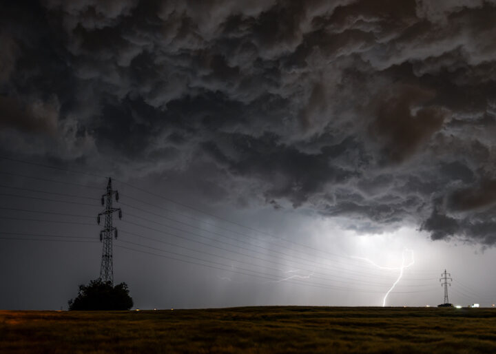 Lightning storm with dark and thick clouds over a field