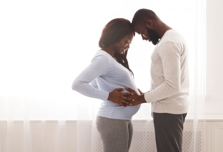 man and woman with hands on her pregnant belly