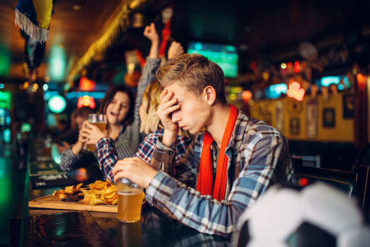 disappointed young man at a bar puts his hand on his face