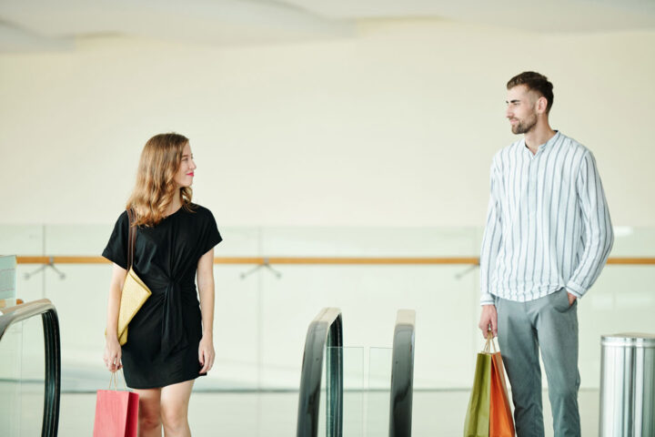 young man and women looking at each others in a shopping center