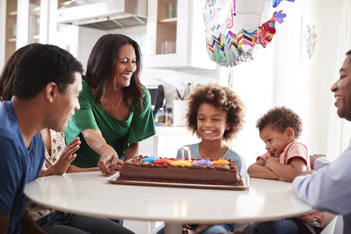 Close up of three generation family sitting together at the kitchen table celebrating the pre-teen daughter's birthday with a birthday cake