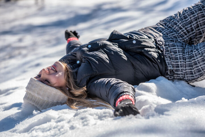 young woman lying happy in the snow