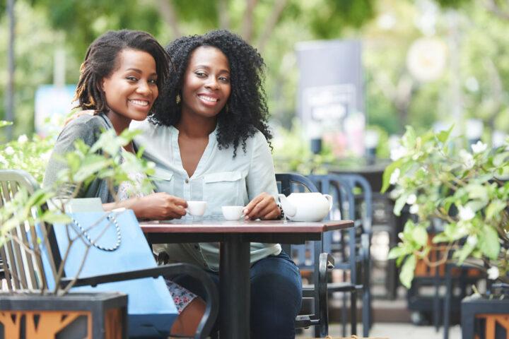 two women drinking coffee outside