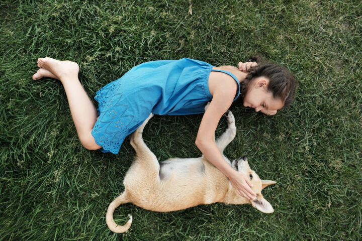 young girl lying on the grass next to her dog