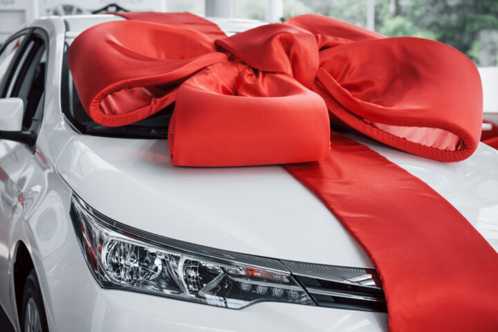 giant red ribbon on a new white car